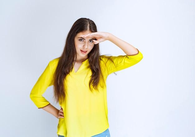 額に手を置いて誰かを観察または探している黄色いシャツの女の子。