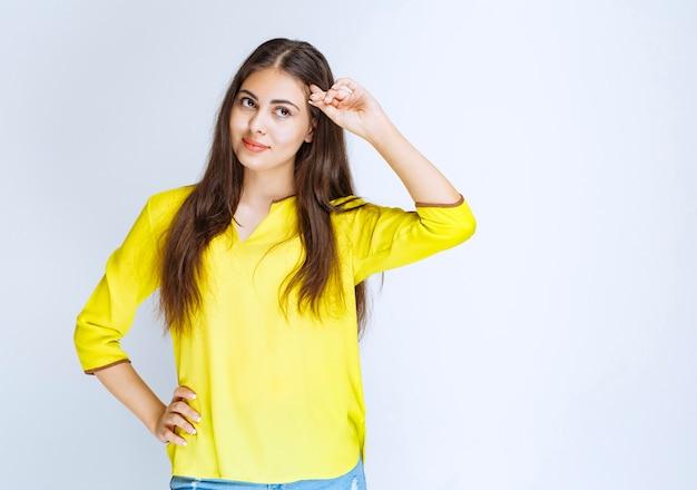 노란 셔츠를 입은 소녀가 이마에 손을 대고 누군가를 관찰하거나 찾고 있습니다.