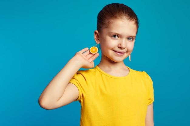 Девушка в желтой рубашке показывает оранжевые серьги и улыбается у синей стены