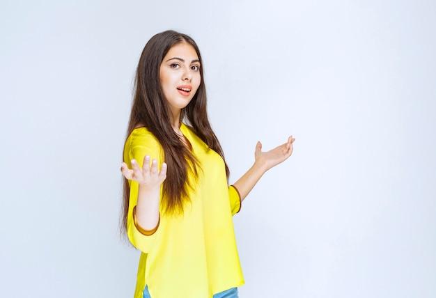 Девушка в желтой рубашке показывает что-то в ее открытой руке.