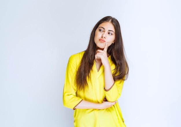 Девушка в желтой рубашке мышления и мозгового штурма.