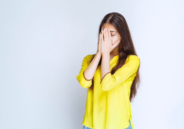 Девушка в желтой рубашке объединяет руки и мечтает.