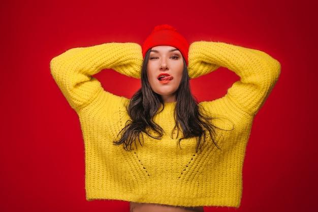 Девушка в желтом свитере и шляпе на красном фоне показывает язык и подмигивает