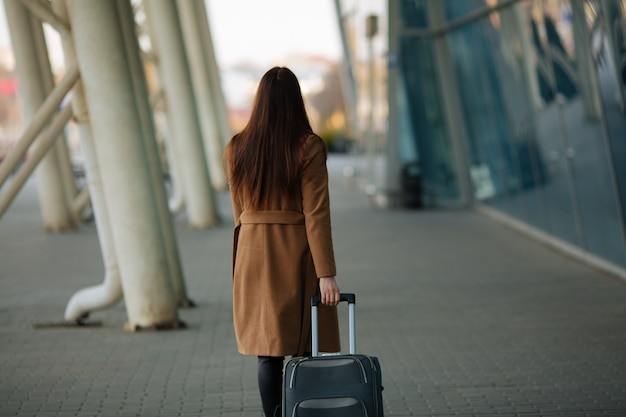 Girl at international airport, luggage and waiting for her flight, view from airport terminal.