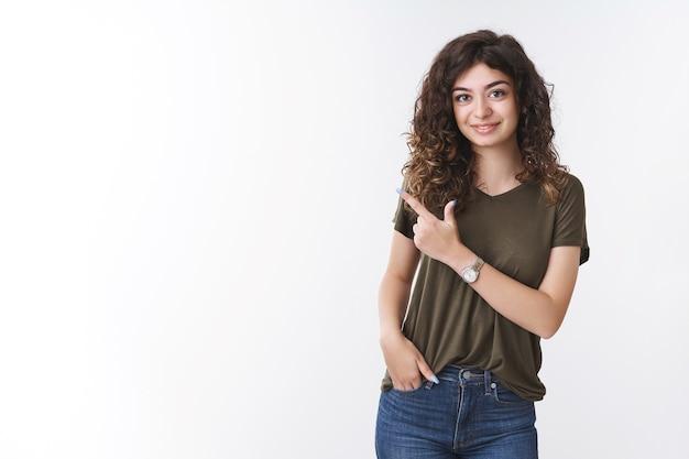 グラブバイトポインティングを招待する女の子は、フレンドリーな笑顔の友好的な友人に立っているポジティブな幸運な白い背景を持ってハンドポケットを持ってカジュアルに非公式の会話を話している