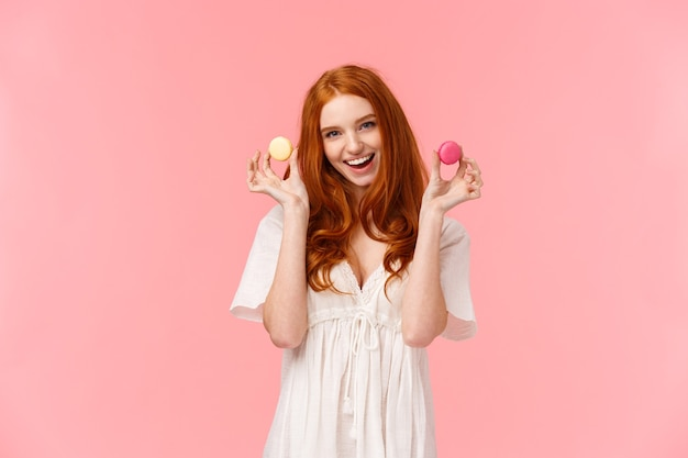 Girl inviting sit with her enjoy tea with desserts. stunning, alluring redhead female in white dress, showing two macarons tempting friend have bite, smiling excited, standing pink background