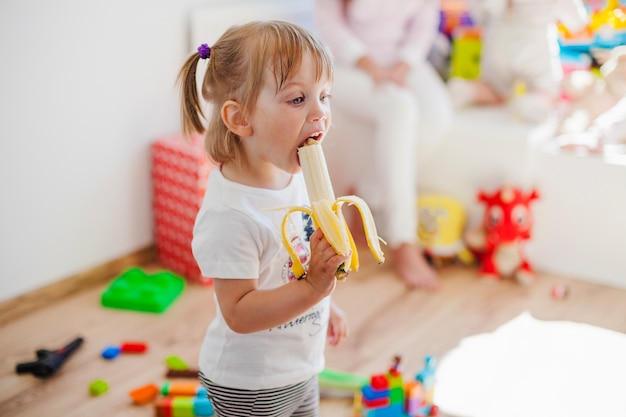 Girl is absorbed with eating banana