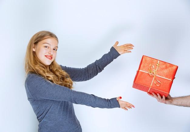女の子は赤いギフトボックスを提供されています。