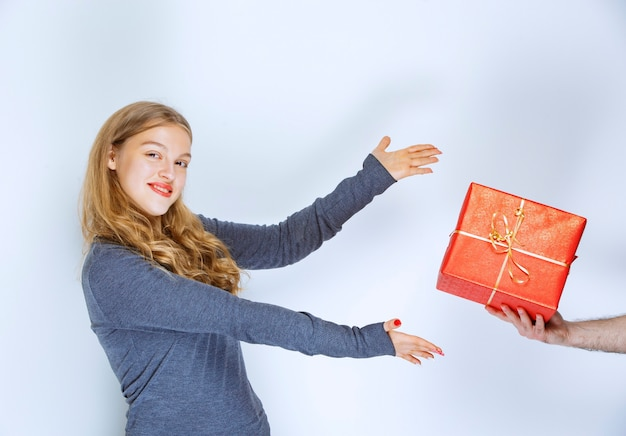 Girl is being offered a red gift box.