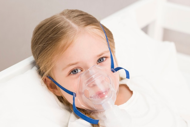Girl is breathing through an inhaler. a sick child is lying on the bed