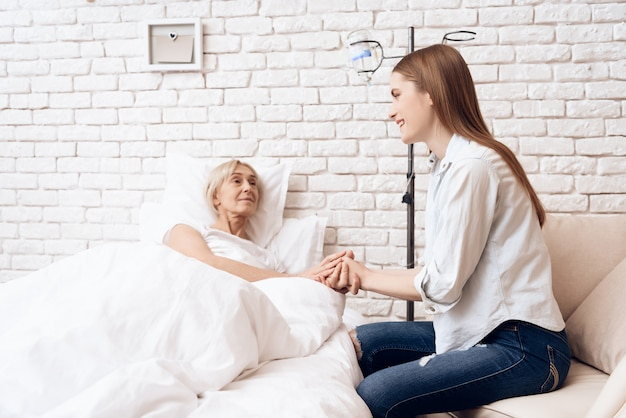 女の子は自宅でベッドで高齢者womaninを気にしています