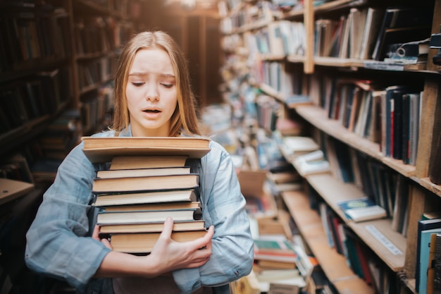 Girl is carrying a lot of books in her hands. it is hard for her to do. she looks hepless and tired. the girl stands in big old library.