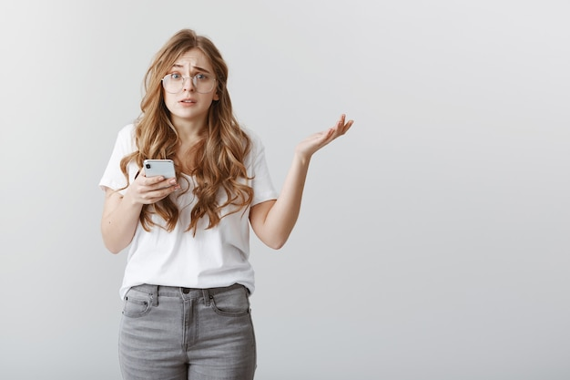 Girl is clueless who sent ridiculous message. portrait of worried confused attractive woman with blond hair in glasses, shrugging, spreading palm in unaware gesture, holding smartphone, being nervous