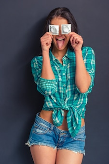 Girl is covering eyes with condoms and showing her tongue.