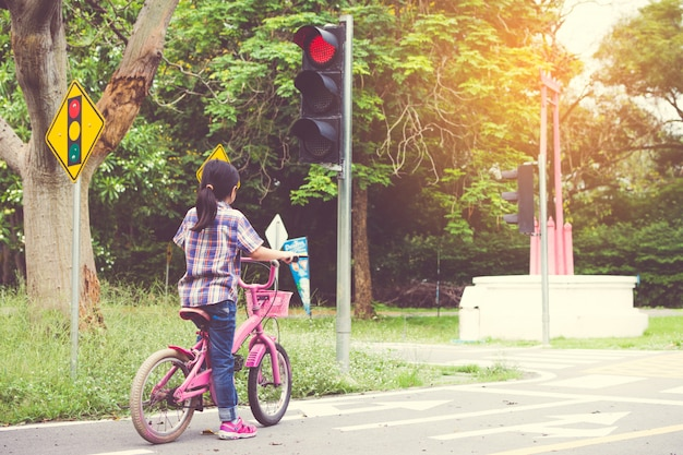 Girl is cycling in the park, bicycle stops at traffic lights
