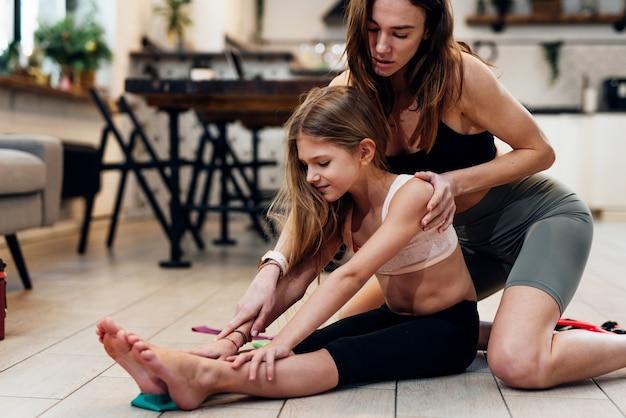 Девушка делает упражнение на растяжку. она сидит на полу с вытянутыми ногами и делает изгиб, а мама ей помогает.
