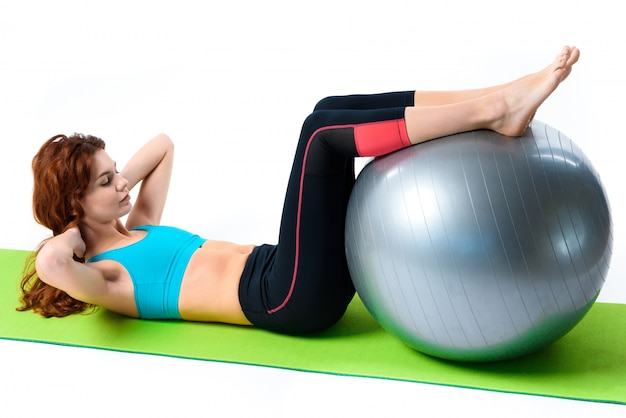 Girl is doing crunch exercises with gym ball.