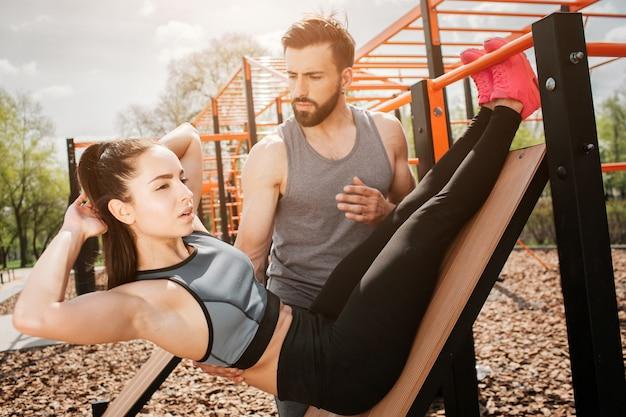 女の子は腹筋運動をしていて、右を向いています。
