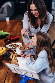 女の子は台所のテーブルで宿題をしていて、母親は彼女に食べ物の味を与えます。