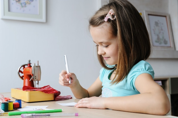 The girl is drawing a sketch of a dress for a doll. to sew it on a sewing machine.