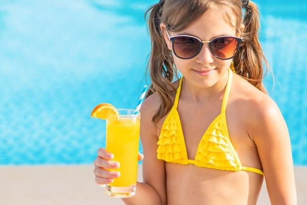 Девушка пьет коктейль у бассейна