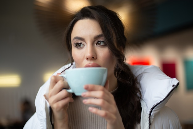 Girl is drinking a hot drink in a cafe