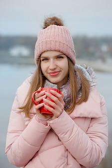 소녀는 빨간 컵에서 차를 마시고있다