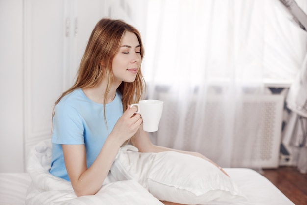 The girl is enjoying the morning, holding a cup with a hot drink in her hands