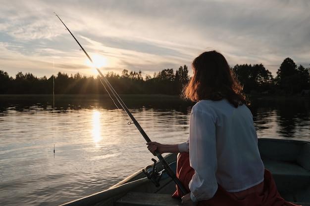 Девушка ловит рыбу с удочкой. девушка сидит в лодке. рыбалка на берегу озера.