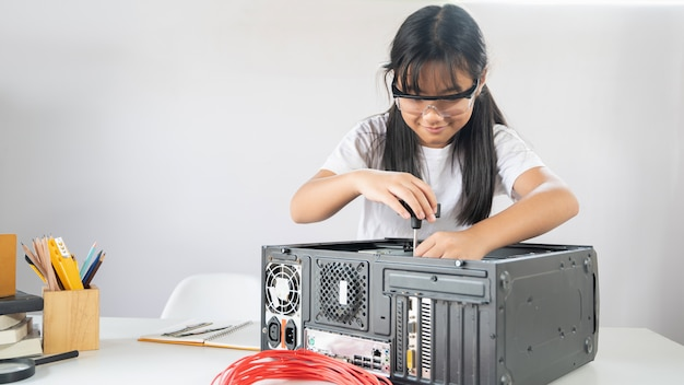 Girl is fixing computer hardware at the modern white working desk.