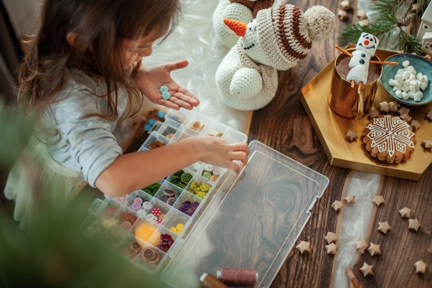 The girl is getting ready for christmas and decorates knitted snowmen with buttons. new year's decor concept. gingerbread cookies are on the table. cocoa and christmas tree branches.