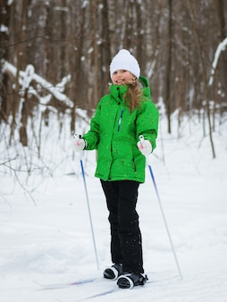 Girl is in a good mood on the slopes in the winter forest.