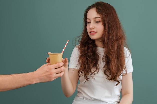 The girl is handed a paper cup with a straw