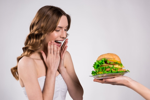 Girl is happy about hamburger isolated.