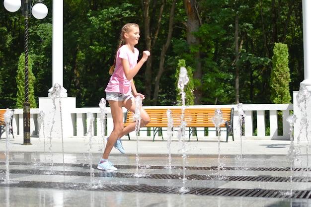 Девушка развлекается в уличном фонтане.