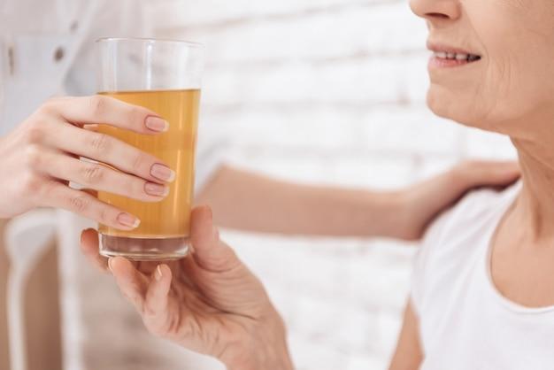 女の子はジュースのガラスで女性を助けています。
