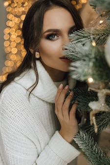 Girl is hiding behind a christmas tree