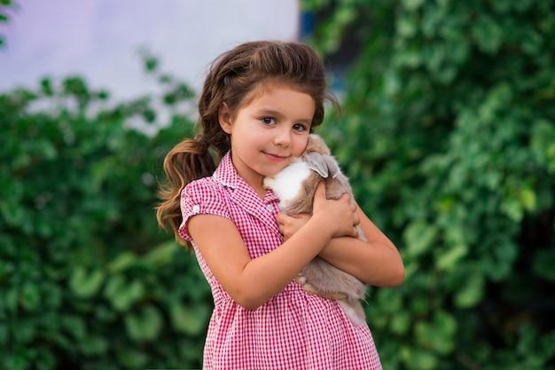 Девушка держит милый маленький кролик, открытый стрелять