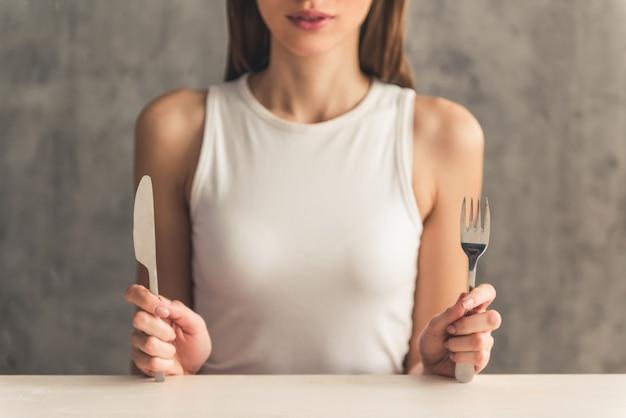 Девушка держит вилку и нож.