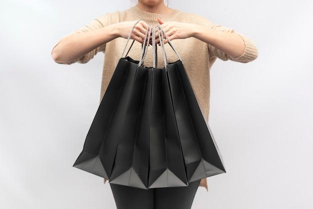 女の子は黒い紙の買い物袋を持っています。紙袋。