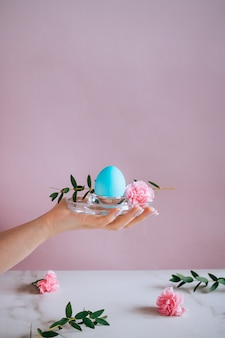 The girl is holding a blue eater egg on a stand, pink and marble background, minimalism, flowers