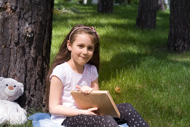 The girl is holding a book under a tree on the green grass. sunny summer vacation, picnic in nature