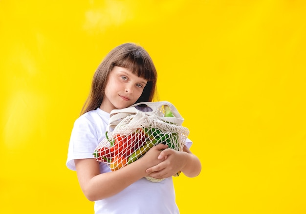 Girl is holding cotton eco-bag with vegetables
