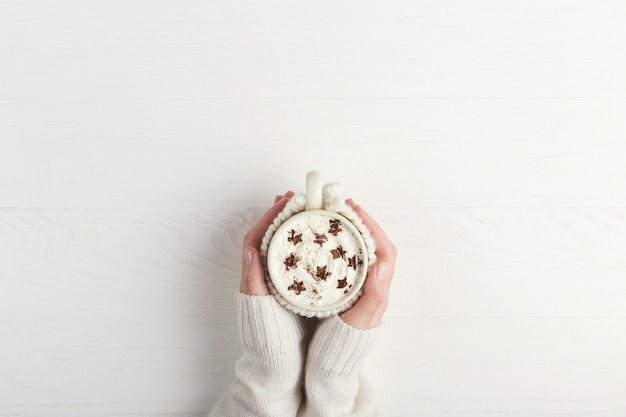 The girl is holding a cup of hot winter drink, with whipped cream and powder in the form of stars