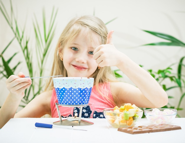The girl is holding a finger up while preparing a chocolate fondue.