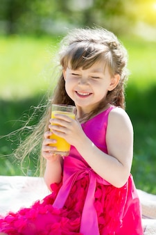 The girl is holding a glass with juice in her hands.