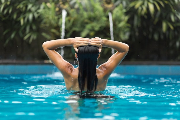 Girl is holding her hands on her head posing in swimpool