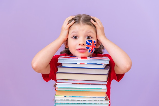 The girl is holding her head because of a difficult study, leaning on a stack of books.