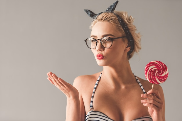 Girl is holding lollipop and sending air kiss