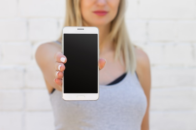 The girl is holding a mobile phone with a blank black screen on an outstretched arm close up